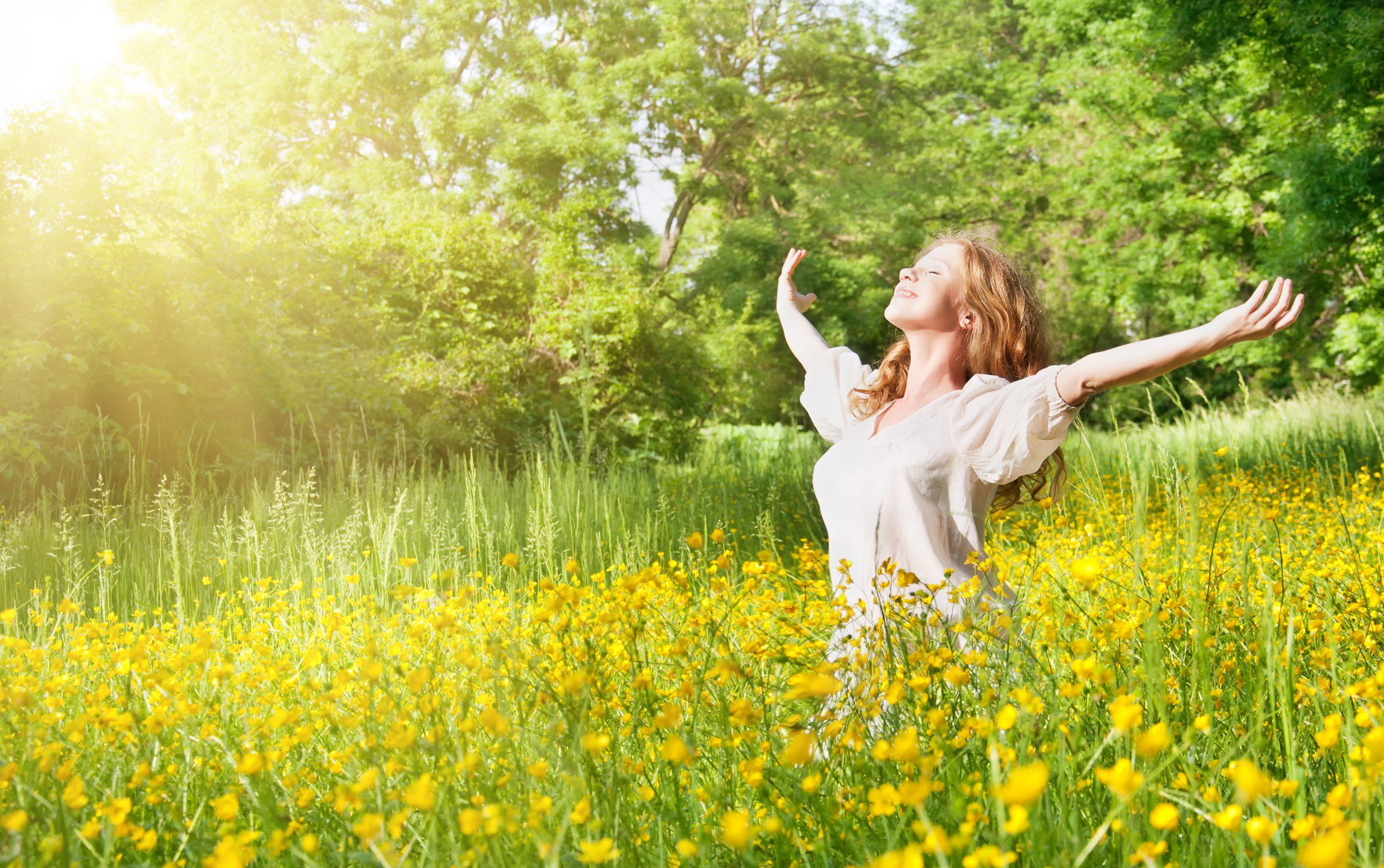 Eine Frau steht in einer Blumenwiese