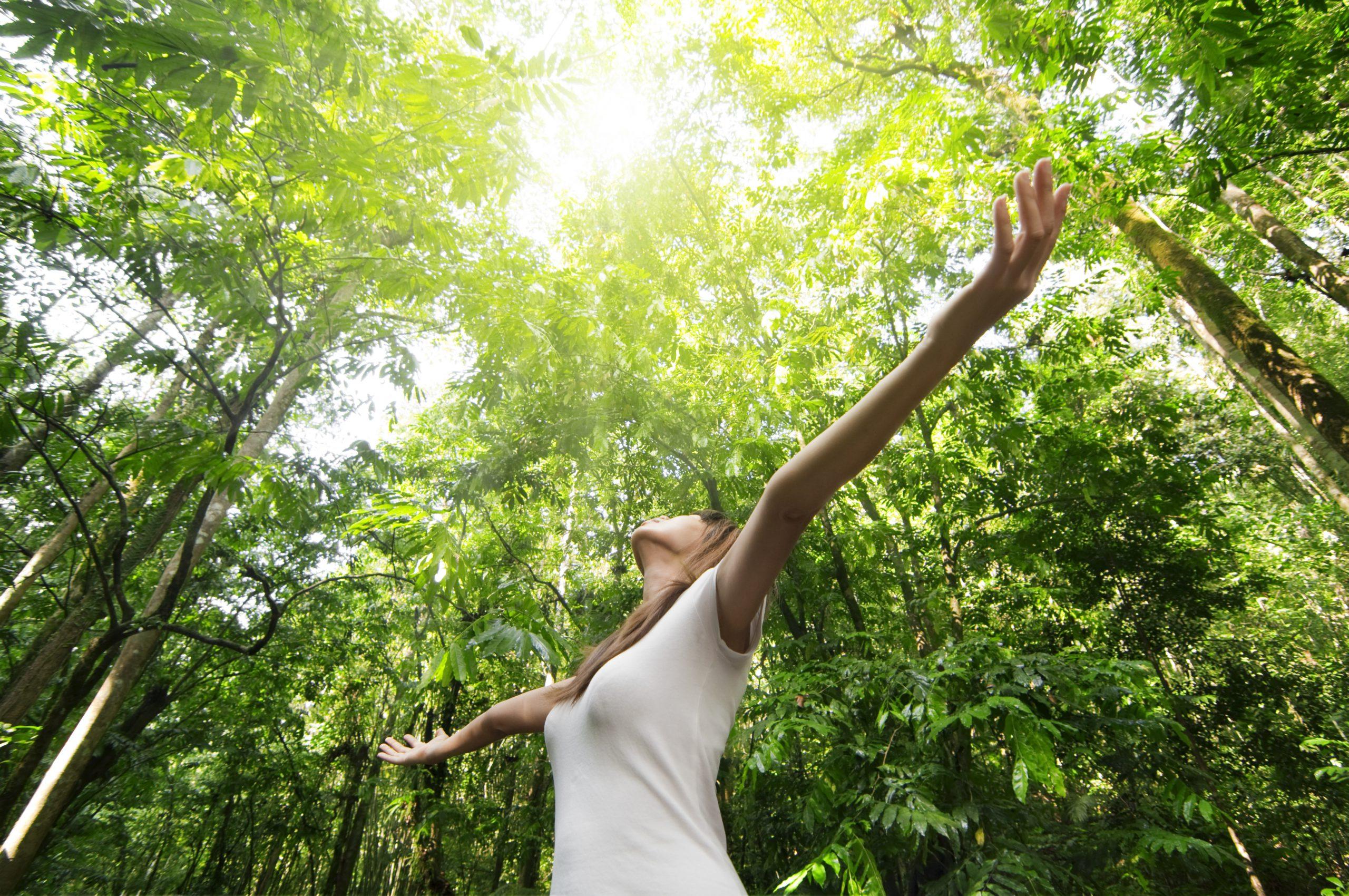 Frau mit offenen Armen im Wald